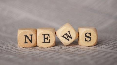 """Das Foto zeigt vier Holzwürfel, die das Wort """"NEWS"""" bilden. Sie stehen auf einem Zeitungsartikel."""