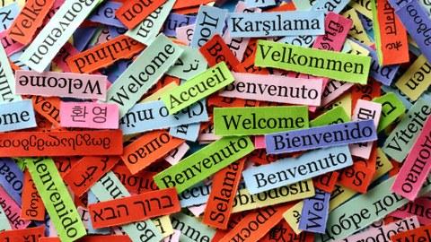 bunte Zettel mit dem Text Willkommen! in verschiedenen Sprachen