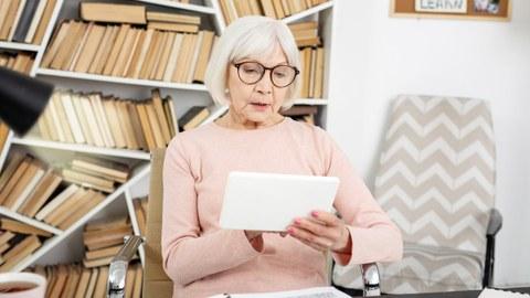 Lesende Seniorin im Arbeitszimmer