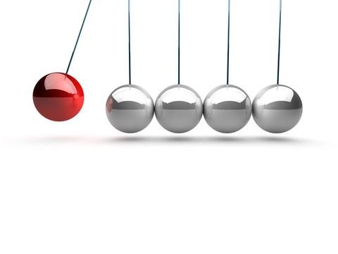 symbolische Darstellung von mehreren silbernen Pendeln in einer Reihe, die durch eine rote Kugel in Bewegung gebracht werden