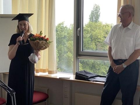 Rede von Dr. Rothländer (links) nach der erfolgreichen Promotion, mit dem Blumenstrauß