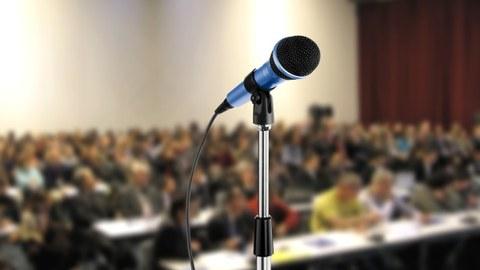 Das Foto zeigt ein Mikrofon, welches vor einem großen Publikum steht.