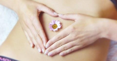 Eine Frau legt ihre Hände auf ihren Bauch. Im Bauchnabel steckt ein Gänseblümchen.