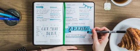 Draufsicht auf Schreibtisch mit ausgefüllten Kalender; Hände einer Person, die in Kalender schreibt
