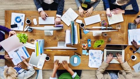 Tisch von oben mit Computern, Laptops und Dokumenten, an dem acht Personen sitzen