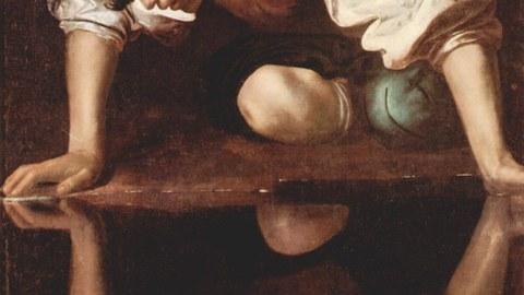 Mann beugt sich über eine Wasseroberfläche und betrachtet sein Spiegelbild