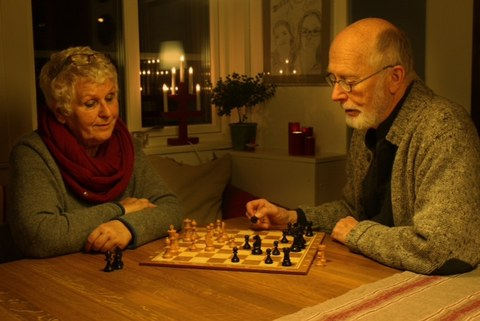 older man and woman play chess