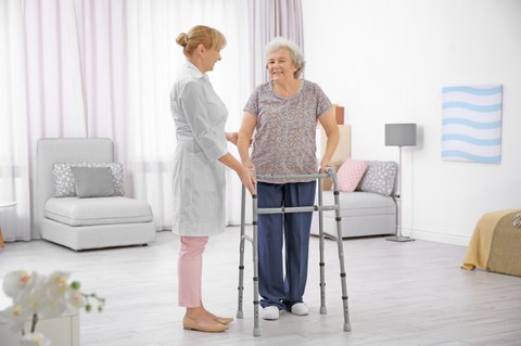 Pflegerin hilft Frau mit Gehhilfe