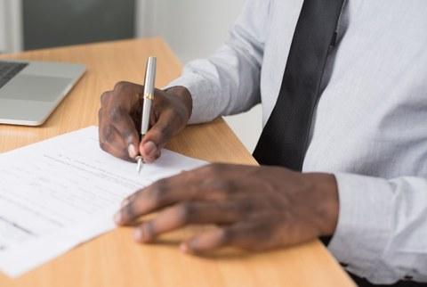 Mann im weißen Hemd unterzeichnet Unterlagen