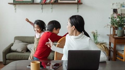 Frau am Laptop, im Hintergrund spielen zwei Kinder im Wohnzimmer