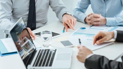 Es sitzen 2 Manger und eine Frau am Tisch, auf dem ein Laptop und Papiere mit Statistiken liegen. Die Haltung einer Hand suggeriert, dass diese Statistiken gerade erläutert werden.