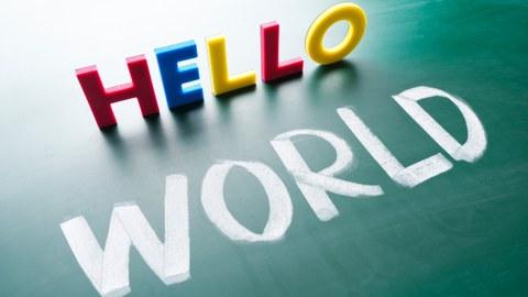 """Das Foto zeigt eine Tafel, auf welche das Wort """"world"""" mit weißer Kreide geschrieben wurde. Darüber ist mit Magnetbuchstaben das Wort """"hello"""" dargestellt."""