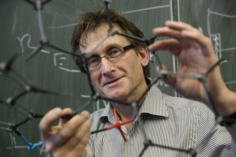 Ben Feringa, Chemie-Nobelpreisträger, hält ein Molekülmodell in die Kamera.