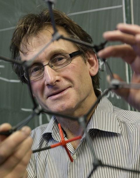Nobelpreisträger Ben Feringa blickt durch ein Molekularmodell
