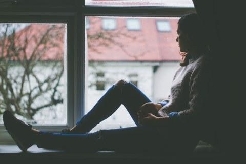 Frau vor dem Fenster sitzend