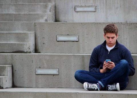 Jugendlicher sitzt auf einer Treppe mit Handy in der Hand.