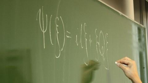 Es ist eine Hand zu sehen, die mit einem Stück weißer Kreide eine mathematische Formel an die Tafel schreibt.