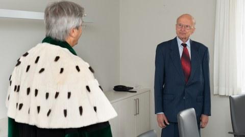 Links ist Rektor Müller-Steinhagen von hinten zu sehen. Mit Gesicht in die Kamera gewand, Prof. Winfried Hacker aufrecht stehend.