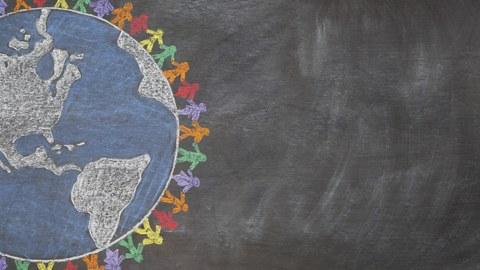 Auf dem Bild ist eine Tafel zu sehen, auf der eine Weltkugel mit Kreide gezeichnet ist. Entlang der Weltkugel sind viele bunte Männchen im Kreis angeordnet und halten sich an den Händen. Die Weltkugel ist am linken Bildrand angeschnitten dargestellt.