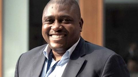 Ein großer farbiger Mann im Anzug mit einen freundlichen Lächeln.