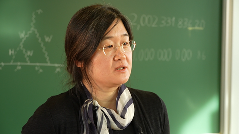 Hyejung Stöckinger-Kim in der Nahaufnahme vor einer grünen Tafel.