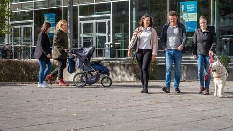 Bild mit einer Gruppe Studierender mit Kinderwagen und Blindenund.