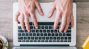 Das Foto zeigt von oben die Hände einer Person, welche eine Tastatur bedienen, daneben sind zur linken Seite eine Pflanze, sowie Kopfhörer und zur rechten Seite ein gelbes Buch.