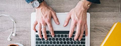 Das Foto zeigt von oben die Hände einer Person, welche eine Tastatur bedienen, daneben liegen zur linken Seite Kopfhörer und zur rechten ein gelbes Buch.