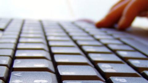Das Foto zeigt eine Nahaufnahme einer Laptoptastatur, sowie die Hand einer Person, welche den Laptop bedient.