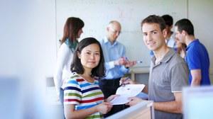 Das Foto zeigt zwei Studierende. Sie stehen sich gegenüber, schauen in die Kamera und halten gemeinsam mehrere Blätter in den Händen. Im Hintergrund erkennt man weitere Personen vor einem Whiteboard.
