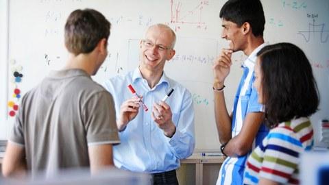 Das Foto zeigt vier Personen vor einem großen, beschriebenen Whiteboard. Sie stehen sich gegenüber und lachen. Eine Person hält zwei Whiteboardmarker in den Händen.
