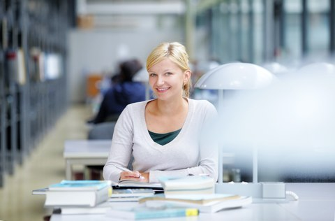 Das Foto zeigt eine Studentin in der Bibliothek. Sie sitzt an einem Tisch und lächelt in die Kamera. Vor ihr liegen viele Bücher.