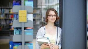Das Foto zeigt eine Studentin in der Bibliothek. Sie steht an einem Pfeiler, hält einige Bücher in den Händen und lächelt in die Kamera.