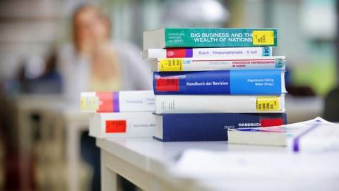 Das Foto zeigt eine Stapel Bücher aus der Bibliothek zum Thema Handel und Finanzen. Sie liegen übereinander auf einem Tisch.