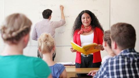 Das Foto zeigt ein Fremdsprachenseminar aus Sicht eines Studierenden. Vor der Tafel im Hintergrund steht die Dozentin. Sie hält ein aufgeschlagenes Buch in den Händen. An der Tafel steht ein Student, der gerade mit einem Stift etwas anschreibt.