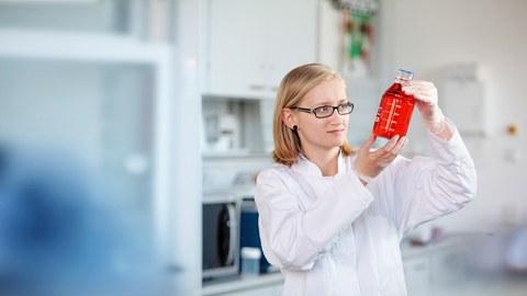 Das Foto zeigt eine Frau mit weißem Laborkittel in einem Labor. In der Hand hält sie ein Glasgefäß mit einer roten Flüssigkeit, welches sie intensiv betrachtet.