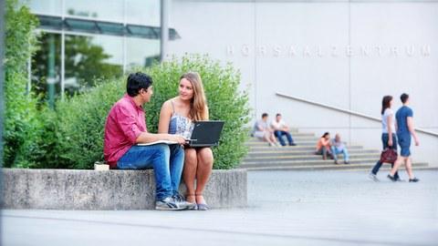Das Foto zeigt zwei Studierende vor dem Hörsaalzentrum der TU Dresden. Sie sitzen auf einer steinernen Abgrenzung und reden miteinander. Während die Frau einen Laptop auf dem Schoß hat, hält der Mann ein Buch in den Händen.