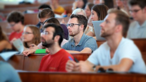 Das Foto zeigt einen Hörsaal voller Studierender. Die Studierenden schauen nach vorn und hören dem Referenten aufmerksam zu. Der Fokus des Bildes liegt lediglich auf einer Person in der Mitte.