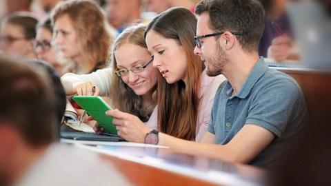 Das Foto zeigt drei Studierende in einem vollen Hörsaal. Sie sitzen nebeneinander und schauen gemeinsam in ein Notebook.