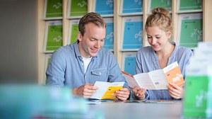 Das Foto zeigt zwei Personen an einem Tisch. Sie halten Informationsflyer zu verschiedenen Studiengängen in den Händen und lesen in diesen. Im Hintergrund erkennt man ein Regal mit weiterem Informationsmaterial zu den verschiedenen Studiengängen.
