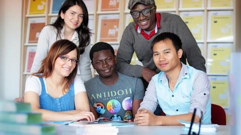 Das Foto zeigt fünf Personen. Sie sitzen bzw. stehen an einem Tisch und lächeln in die Kamera. Auf dem Tisch liegen einige Bücher.