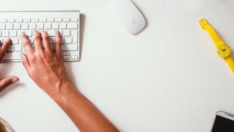 Das Foto zeigt einen weißen Schreibtisch von oben, an welchem eine Person auf einer Tastatur tippt. Auf dem Tisch liegen außerdem eine weiße Computer-Maus, ein Smartphone und eine gelbe Armbanduhr.