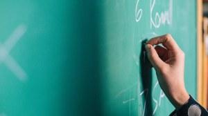 Das Foto zeigt eine grüne Tafel, auf welche eine Person mit weißer Kreide schreibt.