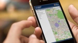 Das Foto zeigt ein Smartphone welches von einer Person genutzt wird. Auf dem Bildshirm des Smartphones ist die Campus Navigator App der TU Dresden geöffnet.