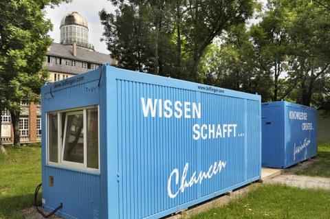 """Das Foto zeigt  zwei blaue Container mit der Aufschrift """"Wissen schafft... Chancen"""" und """"Knowledge creates... fascination"""", welche auf einer Wiese des Campus der TU Dresden stehen."""