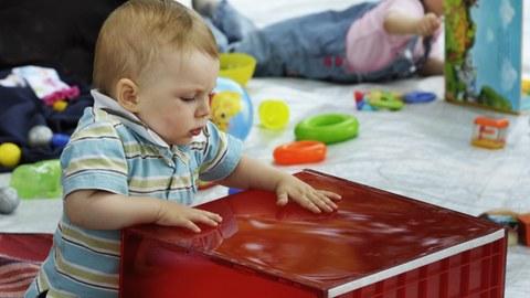 Das Foto zeigt ein Kleinkind, dass mit einer großen roten Kiste spielt. Im Hintergrund blättert ein anderes Kleinkind in einem Buch.