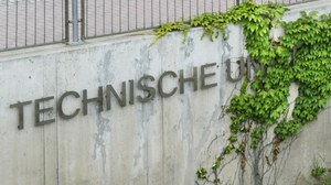 """Das Foto zeigt eine Mauer an welcher der Schriftzug """" Technische Universität"""" angebracht ist. Das Wort """"Universität"""" ist von Efeu überwachsen."""