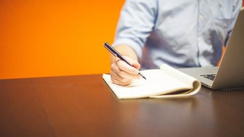Das Foto zeigt eine Person an einem Laptop, welche in ein Notitzheft schreibt.