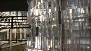 Das Foto zeigt im Vordergrund ein säulenartiges Konstrukt aus gläsernen Fragmenten, in welchen sich Teile des Raumes spiegeln. Im Hintergrund ist durch ein Fenster ein Gebäude zu sehen.