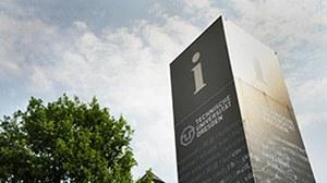 Das Foto zeigt eine Informationssäule der TU Dresden vor leicht bewölktem Himmel.